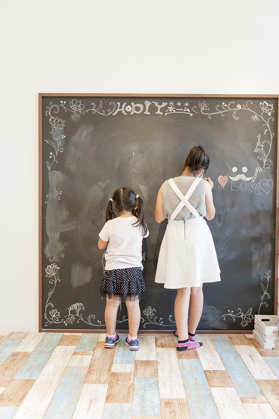 黒板に絵をかく少女